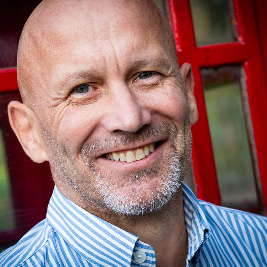 Male client head shot in front of red telephone box