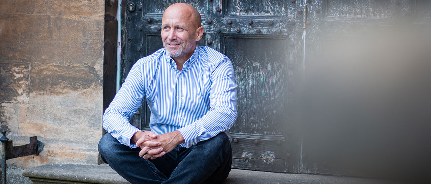 Bald male sat in a doorway, wearing a stripey shirt, smiling and looking into the distance