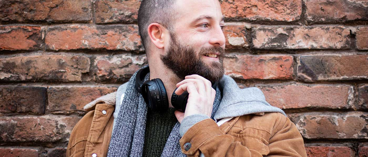 Dating client with headphones around his neck in front of a brick wall