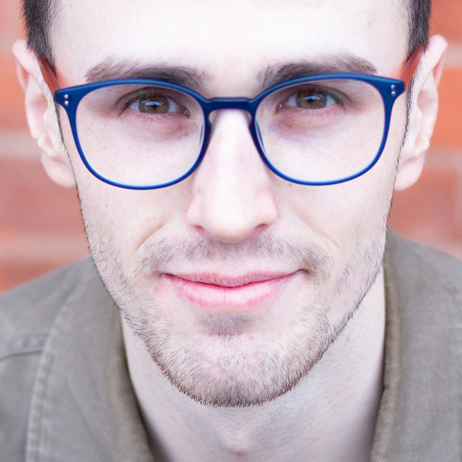 Male looking at the camera in blue-rimmed glasses