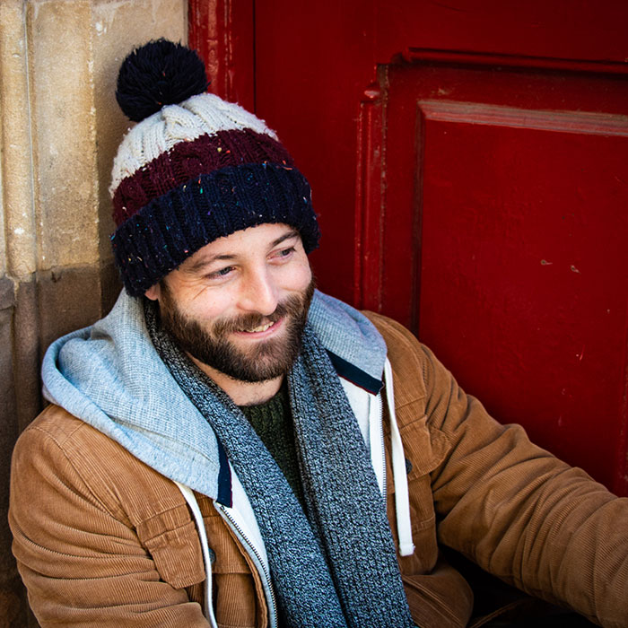 Dating photo of a male in a woolly hat sat in a red doorway