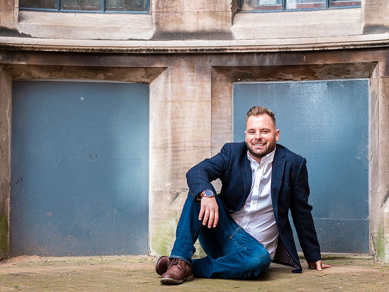 Male sitting on the floor for a photo during his dating photo shoot