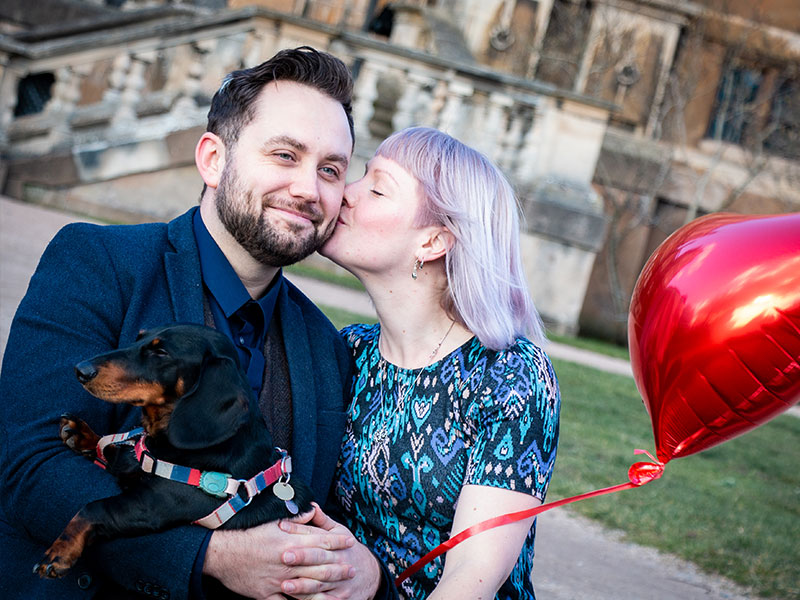 A couple holding their dog and a red love heart balloon