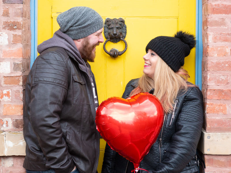 A couple stood in front of a yellow door holding a red love heart balloon