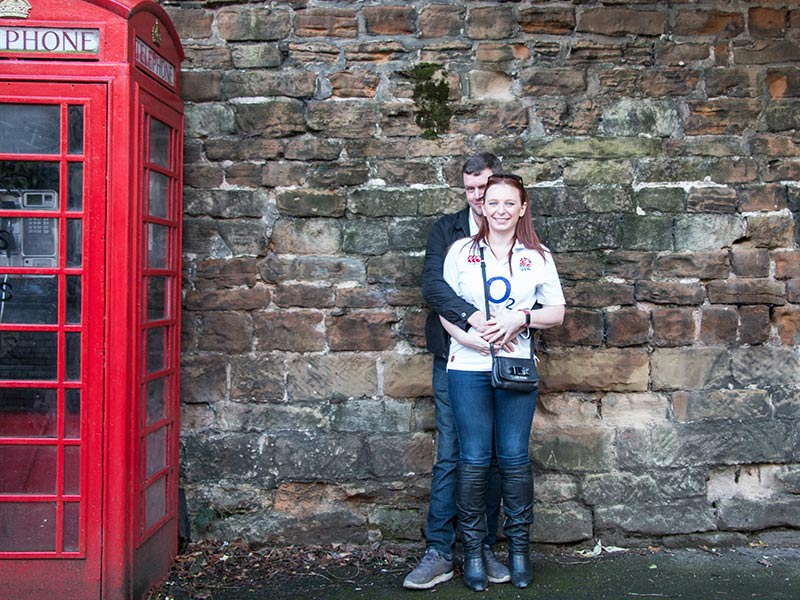 Couple cuddling against a brick wall next to a red telephone box