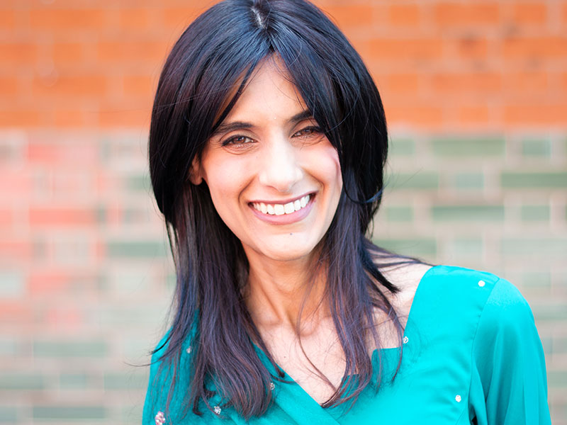 A woman smiling into the camera against a brick wall